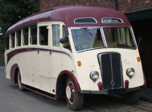 restored white 1930's flat-front bus with a red roof