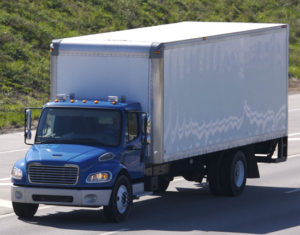 a box truck with a blue cab and white box traveling on a highway