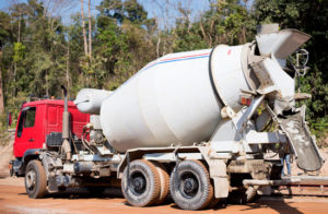 a cement truck with a red cab at a construction site