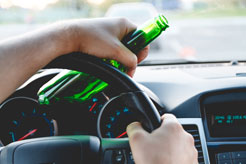 a man with a bottle of beer in his hand driving a car