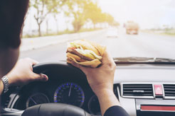 a man eating a hamburger while driving