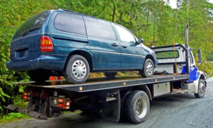 a flatbed truck with a Ford minivan on its bed