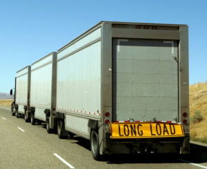 a long combination vehicle with white trailers on a highway