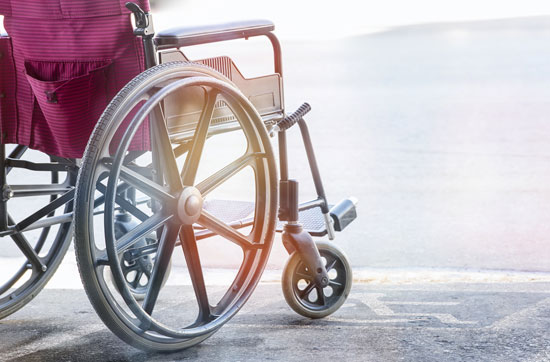 Los Angeles paralysis injury lawyer is available for this person whose red wheelchair is standing in a parking lot