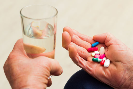an elderly man holding multiple pills on his palm must be defended by a nursing home chemical restraint attorney