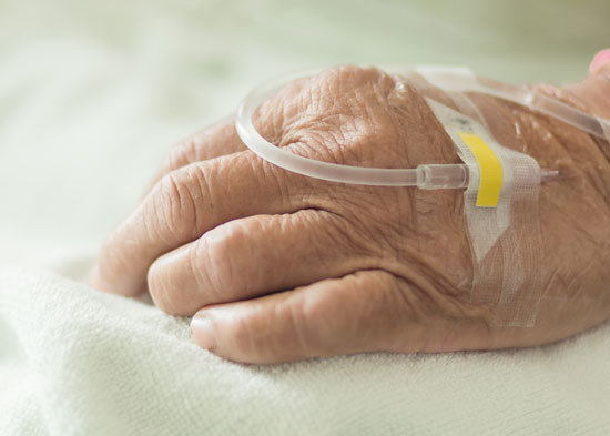 an intravenous line with antibiotics in the hand of a patient who needs a nursing home infections attorney