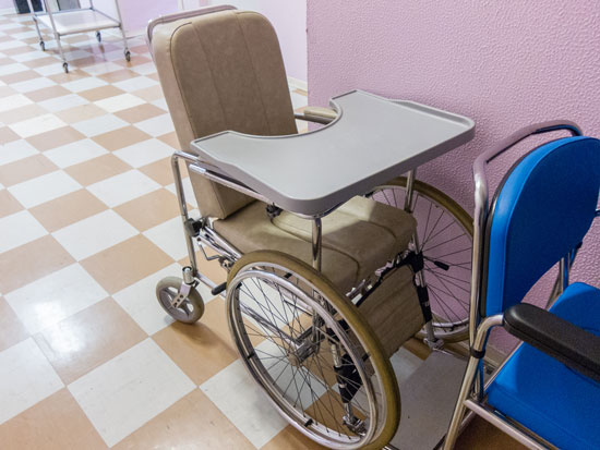 a wheelchair with a tray that can restrain a patient requiring the help of a nursing home physical restraint lawyer