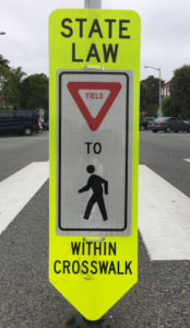 tall yellow pedestrian paddle sign at a crosswalk
