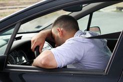 a young man asleep behind the wheel of his moving car