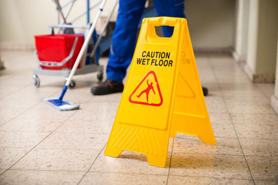 worker washing the floor with a warning sign helps to avoid lawsuits by the slip and fall lawyer Los Angeles trusts