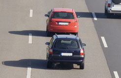 a blue car tailgating a red car on a freeway