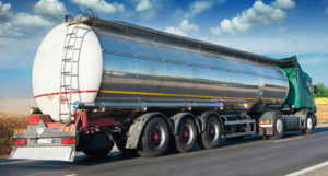 the back view of a shiny polished tanker truck on a highway