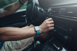 a man adjusting the controls of his car radio while driving