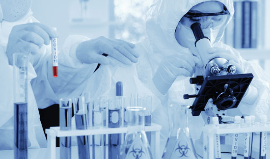 scientists in protective gear in a lab during COVID-19 vaccine clinical trials