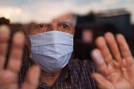 elderly man in a mask behind glass waiting for COVID-19 vaccine