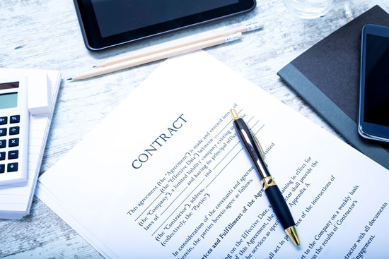 contract, pen, phone, notepad, and other items on the desk of Los Angeles contract litigation attorney